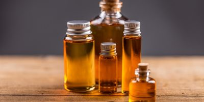 Bottles of essential oil on wooden table