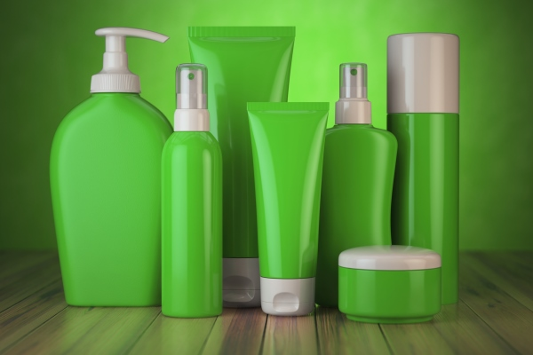 Set of cosmetic products in green containers. Different daily beauty care products like cream, shampoo, lotion, and conditioner