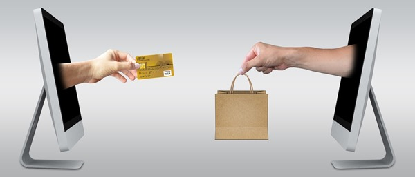 Artistic representation of online buying: two hands coming through computer screens, one holds a credit card to represent a buyer, the other holds a shopping bag to represent a seller.