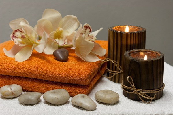 Some Elements of a Massage Therapy: Towels, Candles, Flowers, and Stones