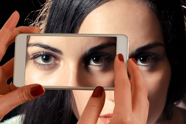 Taking a picture of a beautiful woman with thick, dark eyebrows using a smartphone
