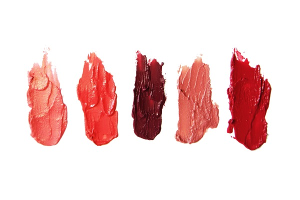 Blots of five different shades of red lipstick on a white background