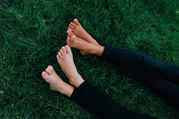 Two pairs of feet lying on the green grass