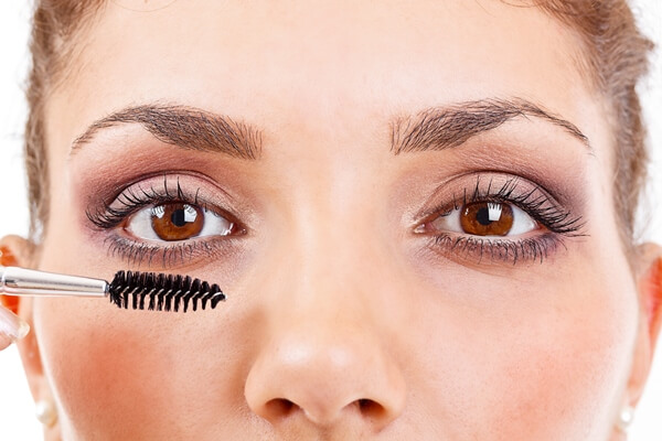 Woman applying castor oil on her eyelashes using mascara wand